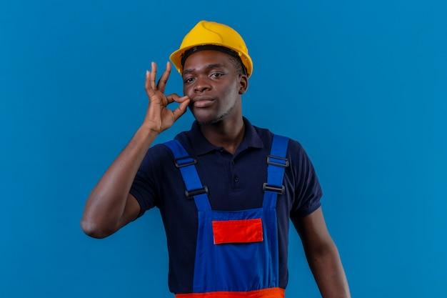 Молодой афро-американский строитель в строительной форме и защитном шлеме делает жест молчания, словно закрывает рот застежкой-молнией на изолированном синем