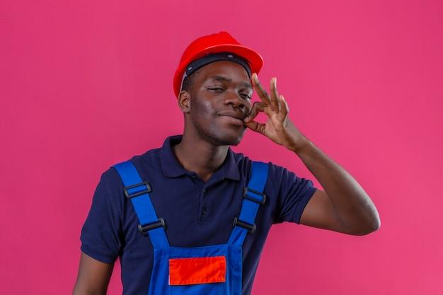 Молодой афро-американский строитель в строительной форме и защитном шлеме делает жест молчания, словно закрывает рот застежкой-молнией на изолированном розовом