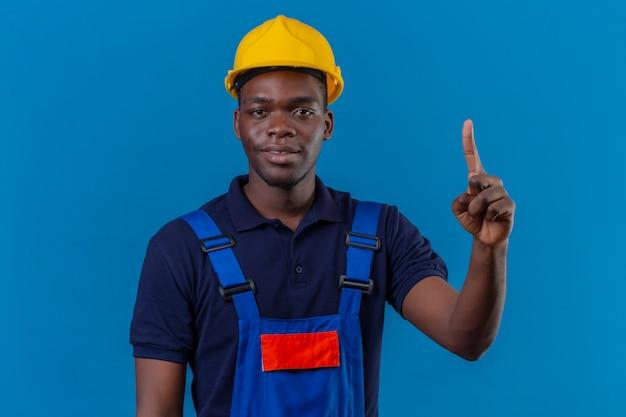 Молодой афро-американский строитель в строительной форме и защитном шлеме, указывая пальцем вверх с уверенным выражением лица, стоя на синем