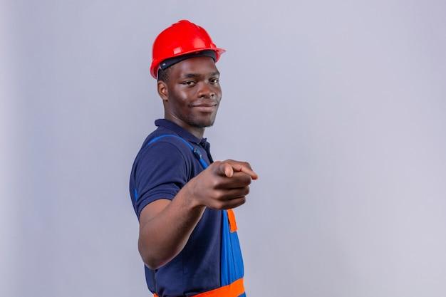 Молодой афро-американский строитель в строительной форме и защитном шлеме, указывая пальцем с уверенной улыбкой