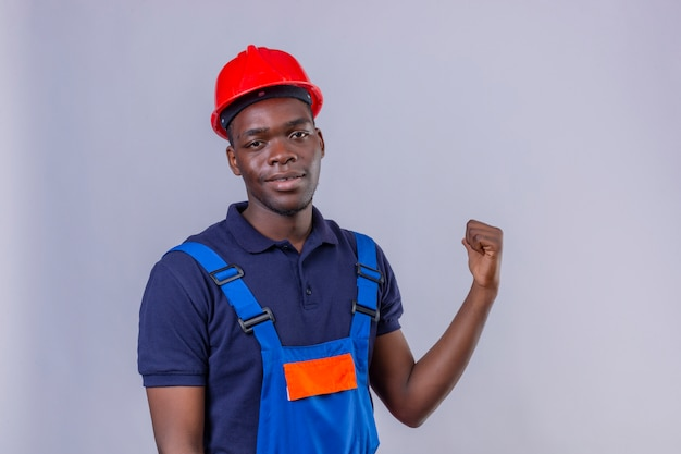 Молодой афро-американский строитель в строительной форме и защитном шлеме, указывая на спину рукой и большим пальцем вверх, улыбаясь уверенно стоя