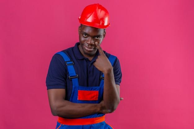Молодой афро-американский строитель в строительной форме и защитном шлеме, указывая в глаза, наблюдая, как вы жестикулируете с подозрительным выражением лица, стоя на изолированном розовом