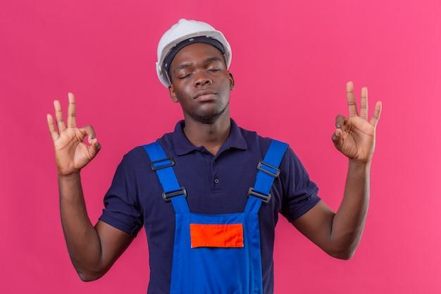 建設ユニフォームと安全ヘルメットを身に着けている若いアフリカ系アメリカ人ビルダー男リラックスして目を閉じてピンクの上に立って指で瞑想ジェスチャーをして閉じた