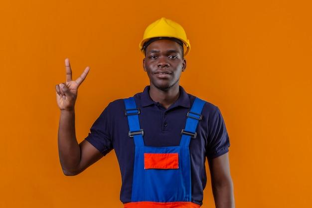 건설 유니폼 및 안전 헬멧을 착용하고 고립 된 오렌지에 자신감을 웃고있는 동안 손가락 2 번으로 가리키는 젊은 아프리카 계 미국인 작성기 남자