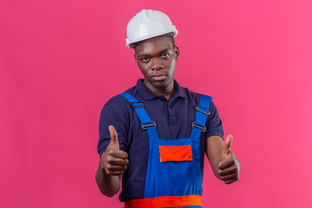Молодой афро-американский строитель в строительной форме и защитном шлеме показывает палец вверх, стоя на розовом