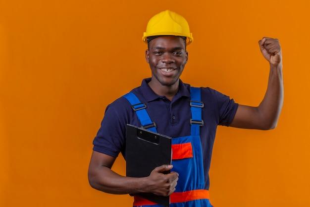 Молодой афро-американский строитель мужчина в строительной форме и защитном шлеме, стоящий с буфером обмена, поднимая руку, сжимая кулак, улыбаясь, стоя с счастливым лицом, празднуя победу