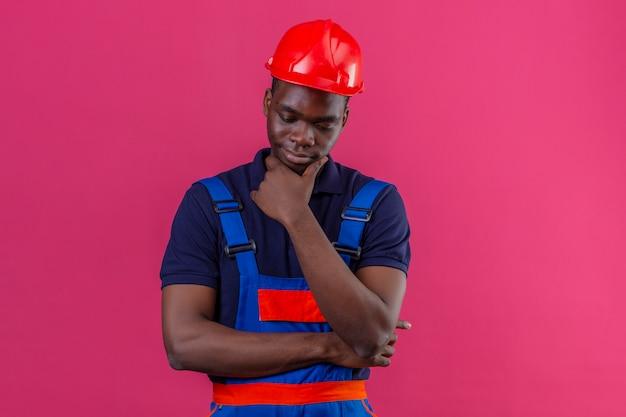 分離のピンクに疑問を持つ選択をしようとすると、あごの思考に手で建設ユニフォームと安全ヘルメット立っている身に着けている若いアフリカ系アメリカ人ビルダー男