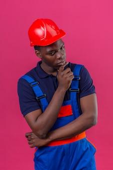 孤立したピンクの顔に真剣な表情で考えてあごに手で建設ユニフォームと安全ヘルメット立っている身に着けている若いアフリカ系アメリカ人ビルダー男