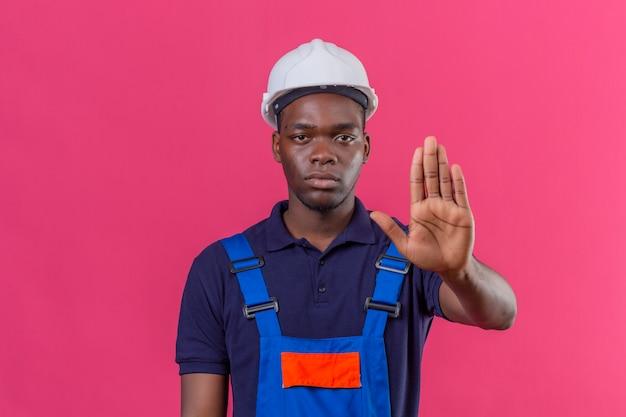 Молодой афро-американский строитель в строительной форме и защитном шлеме, стоящий с открытой рукой и делающий знак остановки с серьезным и уверенным выражением лица, защищающий жест