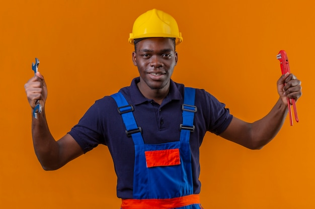Giovane costruttore afroamericano che indossa l'uniforme da costruzione e casco di sicurezza che tiene le chiavi regolabili nelle mani alzate con la faccia felice che sta sull'arancia
