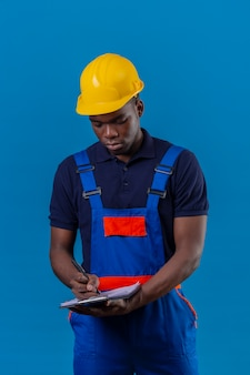 Young african american builder man wearing construction uniform and safety helmet holding clipboard making notes with pen standing on blue