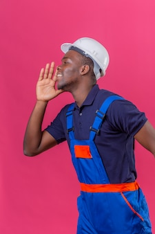 Young african american builder man wearing construction uniform and safety helmet shouting calling someone with hand near mouth standing on pink