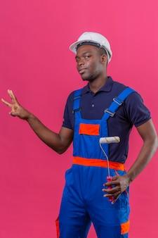 Giovane costruttore afroamericano che indossa l'uniforme da costruzione e casco di sicurezza che mostra e rivolto verso l'alto con le dita numero tre mentre sorride fiducioso sul rosa isolato