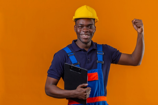 Young african american builder man wearing construction uniform and safety helmet standing with clipboard raising hand clenching fist smiling standing with happy face celebrating victory