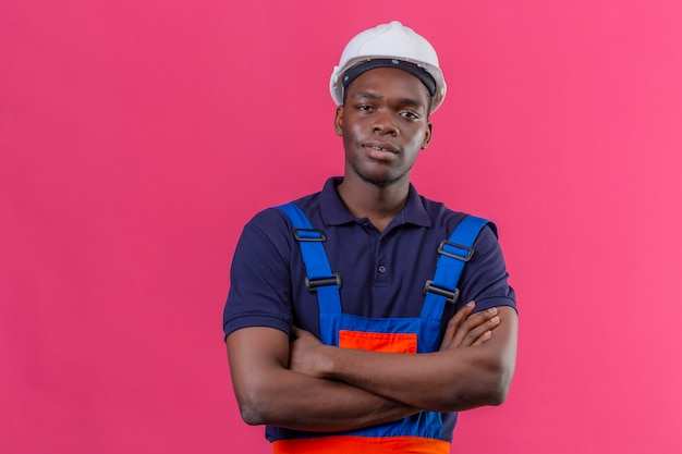 Young african american builder man wearing construction uniform and safety helmet standing with crossed arms on chest looking confident on isolated pink
