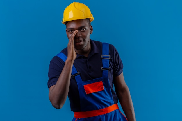 Giovane costruttore afroamericano che indossa l'uniforme da costruzione e il casco di sicurezza in piedi con una mano vicino alla bocca che dice un segreto sul blu isolato