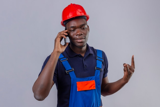 Young african american builder man wearing construction uniform and safety helmet talking on mobile phone making rock symbol smiling standing