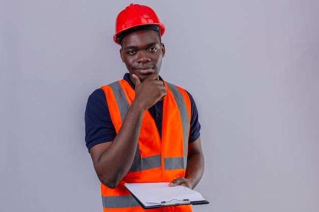 Молодой афро-американский строитель в строительном жилете и защитном шлеме, положив руку на подбородок с уверенной улыбкой
