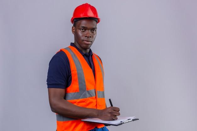 Giovane costruttore afroamericano che indossa la maglia della costruzione e il casco di sicurezza che tiene appunti e penna con la condizione seria del fronte