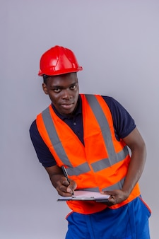 Giovane costruttore afroamericano che indossa la maglia della costruzione e la lavagna per appunti della tenuta del casco di sicurezza che scrive qualcosa con la condizione sicura di sorriso