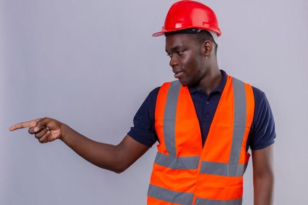 Giovane costruttore afroamericano che indossa la maglia della costruzione e il casco di sicurezza che osserva da parte e che indica con il dito in piedi di lato