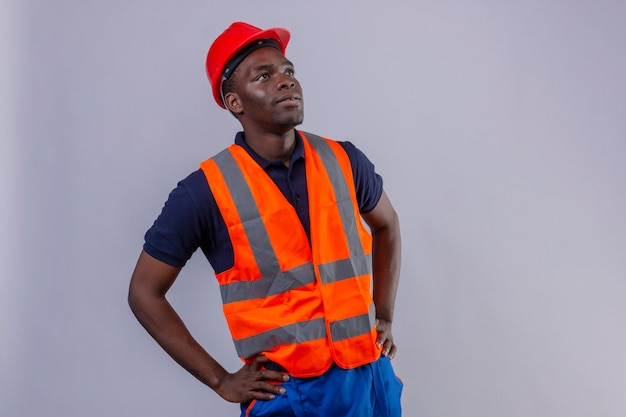 Young african american builder man wearing construction vest and safety helmet looking up with serious face standing