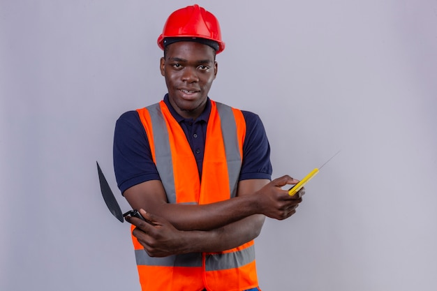 Young african american builder man wearing construction vest and safety helmet standing with arms crossed holding putty knife looking confident