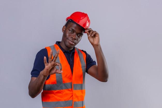 Giovane costruttore afroamericano che indossa giubbotto di costruzione e casco di sicurezza con il sorriso sul viso che fa segno giusto toccando il suo casco in piedi