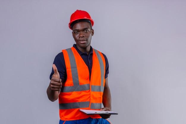 Giovane costruttore afroamericano che indossa giubbotto di costruzione e casco di sicurezza con il sorriso sul viso che mostra il pollice in piedi