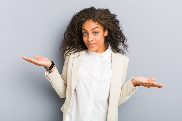 Young african american business woman doubting and shrugging shoulders in questioning gesture.