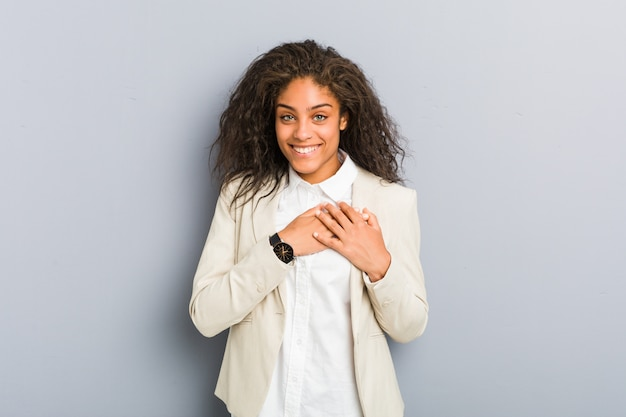Young african american business woman has friendly expression, pressing palm to chest. love concept.