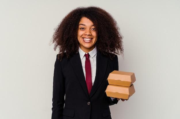 幸せ、笑顔、陽気な白い背景で隔離のハンバーガーを保持している若いアフリカ系アメリカ人のビジネス女性。