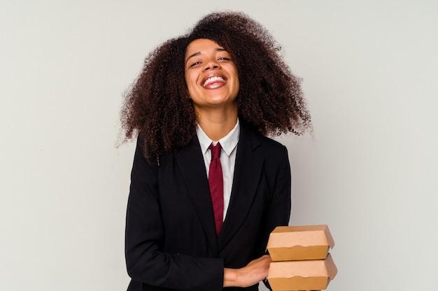 笑って楽しんでいる白い背景に隔離されたハンバーガーを持った若いアフリカ系アメリカ人ビジネス女性。