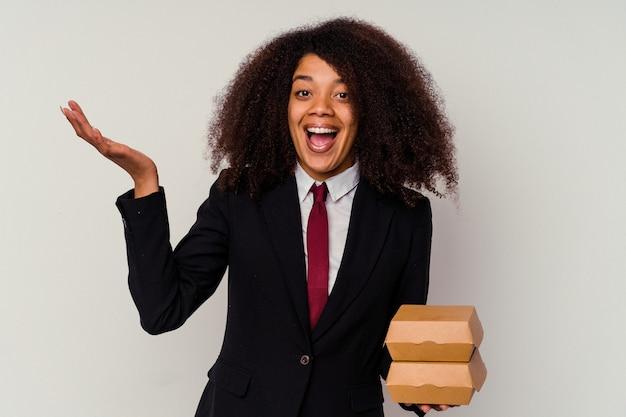 즐거운 놀라움을 받고, 흥분하고 손을 올리는 흰색 배경에 고립 된 햄버거를 들고 젊은 아프리카 계 미국인 비즈니스 여자.