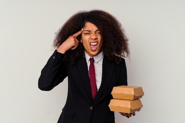 人差し指で失望のジェスチャーを示す白い背景に分離されたハンバーガーを保持している若いアフリカ系アメリカ人ビジネス女性。