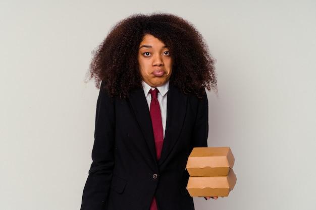 白い背景にハンバーガーを持った若いアフリカ系アメリカ人のビジネスウーマンは肩をすくめ、目を開けて混乱している.