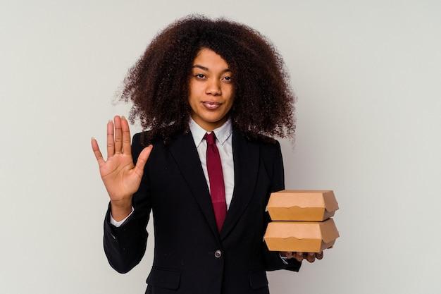 白い背景にハンバーガーを持った若いアフリカ系アメリカ人のビジネスウーマンが、一時停止の標識を示して手を差し伸べて立って、あなたを防ぎます。