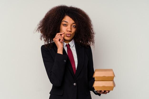 秘密を守る唇に指で白い背景で隔離のハンバーガーを保持している若いアフリカ系アメリカ人ビジネス女性。