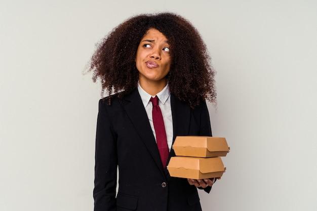 白で隔離のハンバーガーを持っている若いアフリカ系アメリカ人のビジネスウーマンは混乱し、疑わしくて不安を感じています。
