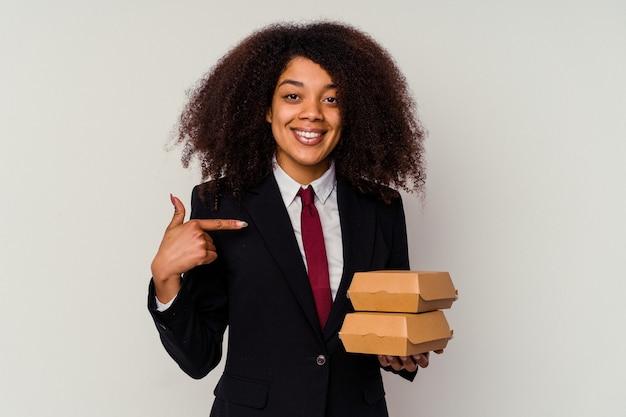 誇りと自信を持って、シャツのコピースペースを手で指している白人に孤立したハンバーガーを保持している若いアフリカ系アメリカ人のビジネス女性