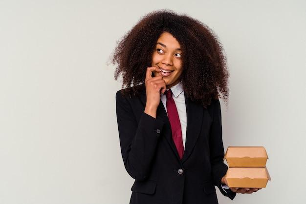 白で隔離のハンバーガーを保持している若いアフリカ系アメリカ人のビジネス女性は、コピースペースを見ている何かについて考えてリラックスしました。