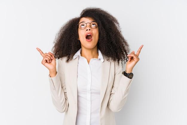 開いた口で逆さまに指している若いアフリカ系アメリカ人ビジネスの女性。