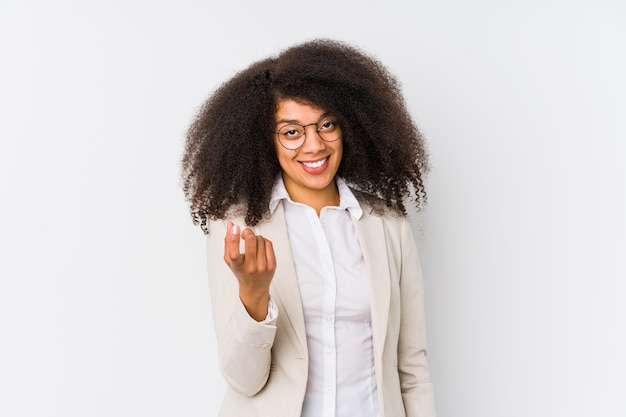 Young african american business woman pointing with finger at you as if inviting come closer.