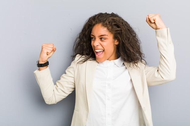 若いアフリカ系アメリカ人ビジネスの女性の勝利、勝者の概念の後拳を上げます。
