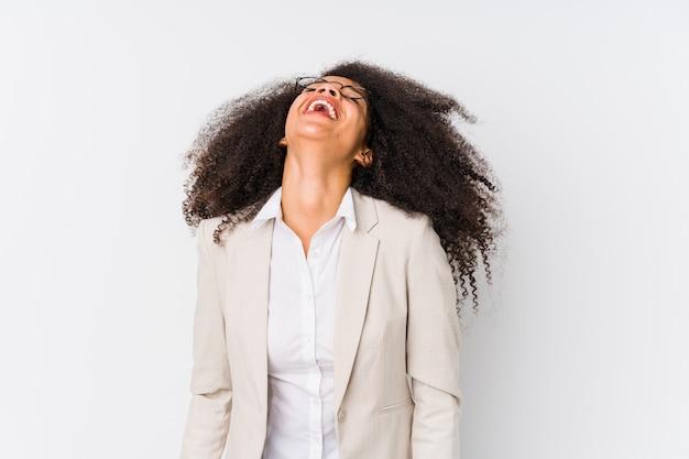 若いアフリカ系アメリカ人のビジネスウーマンはリラックスして幸せな笑い、首を伸ばして歯を見せています。