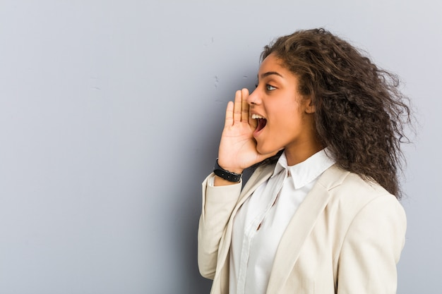Young african american business woman shouting and holding palm near opened mouth.