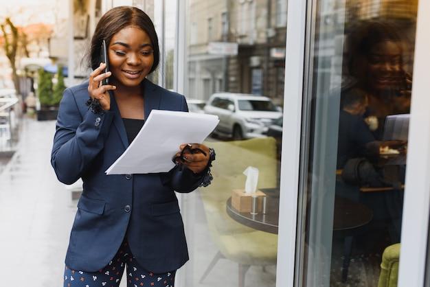 Молодая афро-американская бизнес-леди, стоя возле наружной стеклянной стены.