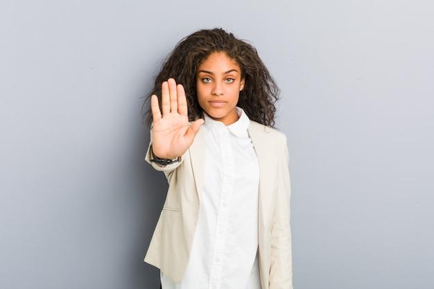若いアフリカ系アメリカ人ビジネスの女性は、差し出された一時停止の標識を示す手を立って、あなたを防ぎます。