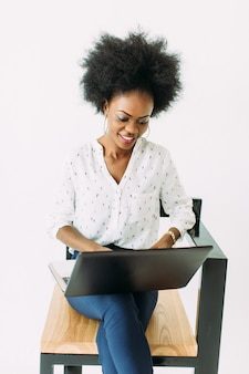 Young african american business woman typing on laptop while sitting on the chair, isolated on white