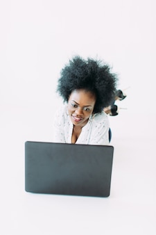 Young african american business woman using the laptop, while lying on the floor, isolated